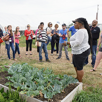 Immersion learning tour of Detroit takes conference attendees to a local community garden where they learned about its impact on the neighborhood.