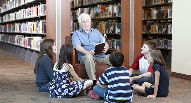 Senior citizen reads to children.
