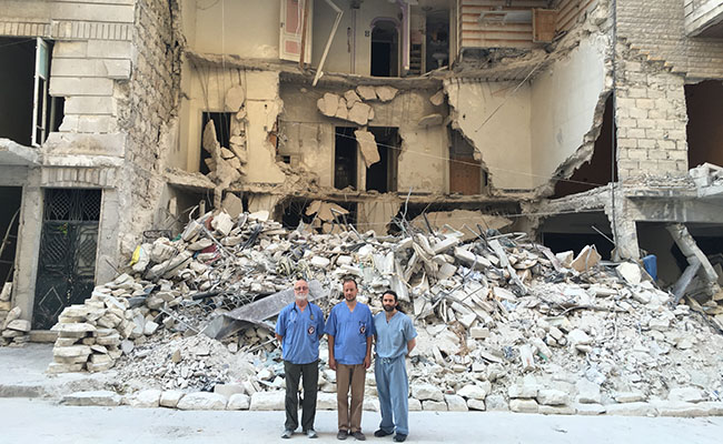 Kahler, Sahloul and Attar in front of a building destroyed by a barrel bomb.