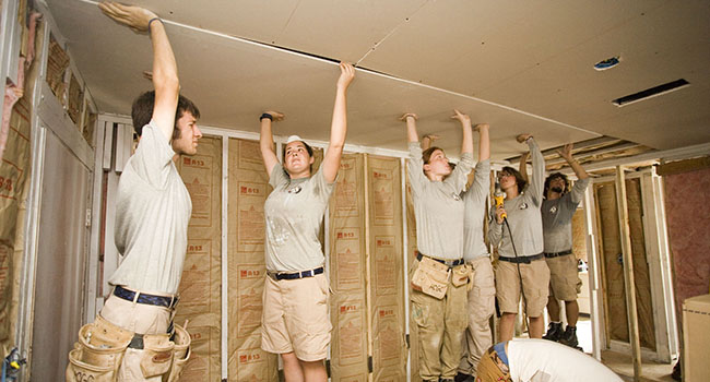 AmeriCorps members working with HandsOn Gulf Coast place a new ceiling in a Biloxi, Mississippi, home damaged by Hurricane Katrina.