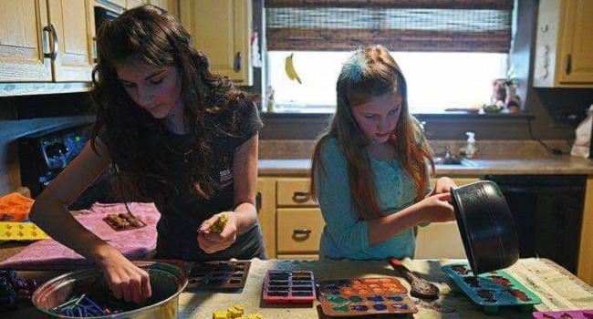 Abby and Riley Neff make crayons in their kitchen.