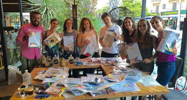 Volunteers with Ethelon pack activity kits for refugee children.