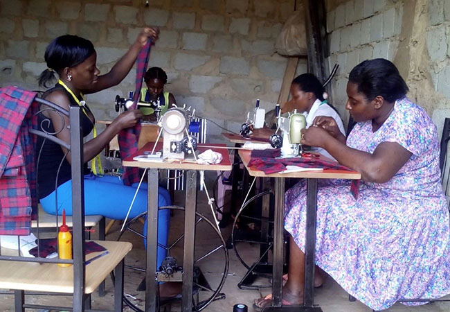 Women assembling MoonCatcher kits at a sewing guild housed in the Women's Resource Center in Jinja, Uganda./Courtesy Ellie von Wellsheim