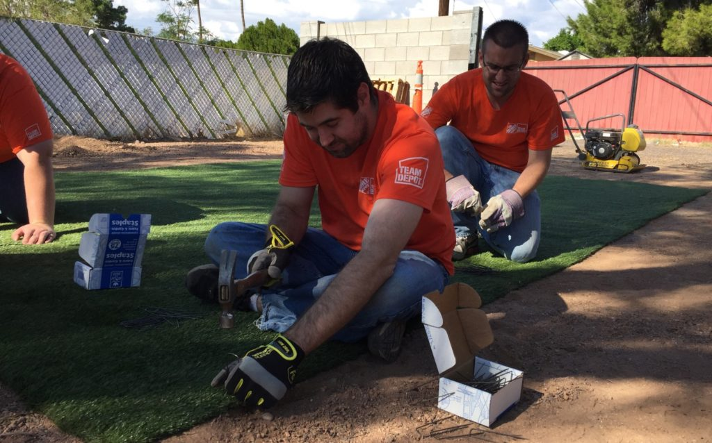 Home Depot volunteers install turf to make a play area for the veteran homeowner's foster children, a project organized through the HandsOn Greater Phoenix Veteran Home Improvement Program.