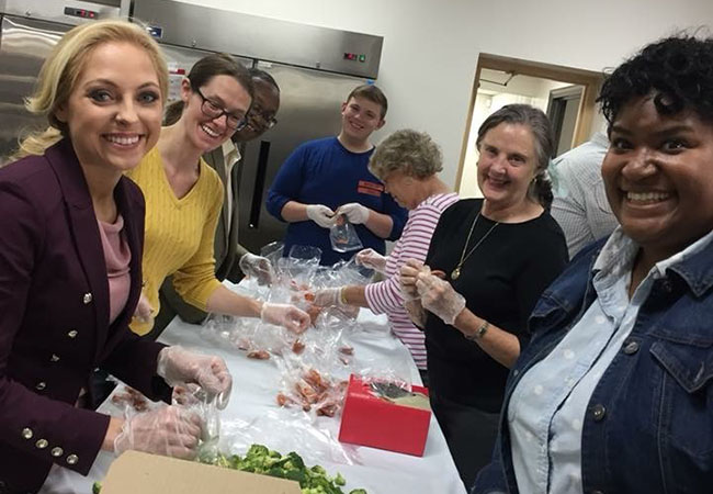 Andrea Hill, right, is joined by Miss Tennessee Caty Davis and fellow Volunteer Tennessee board members for a food preparation service project at the YMCA of Metropolitan Chattanooga.