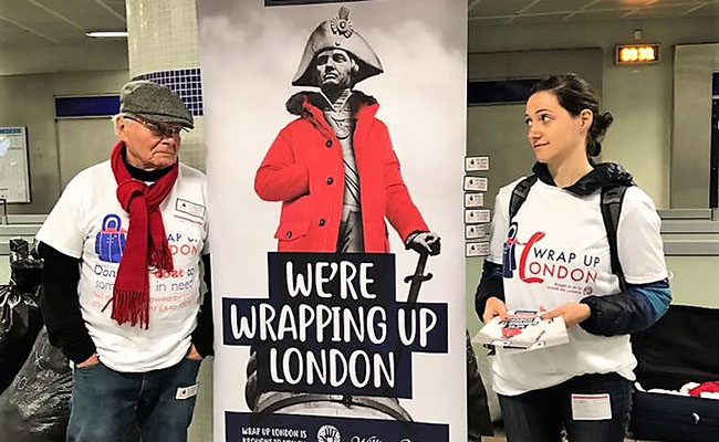 Hands On London volunteers promote the annual Wrap Up London coat drive at a Tube station, with a poster of Napoleon Bonaparte in a bright red, fur-trimmed coat.
