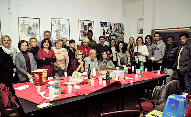 Volunteers gather for a Christmas party at Casa Africa, an organization dedicated to helping immigrants assimilate to life in Rome. Recruited by RomAltruista, volunteers teach newcomers to read and speak Italian so they can find employment.
