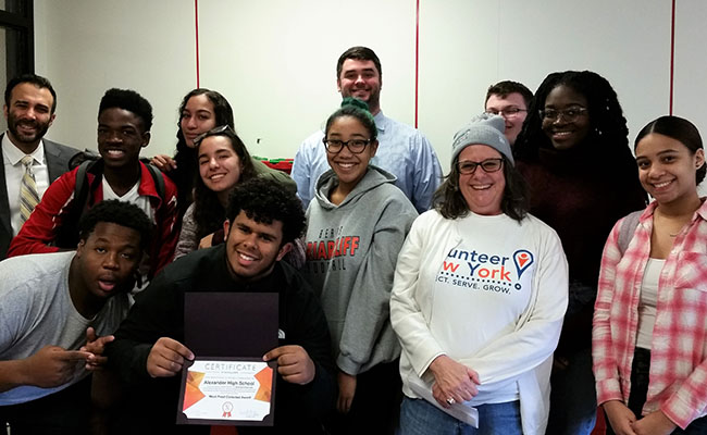 High school students show off their certificate of achievement after raising food donations for the needy during the Un-Hunger Games competition, run by the Volunteer New York! Hunger Relief Corps.