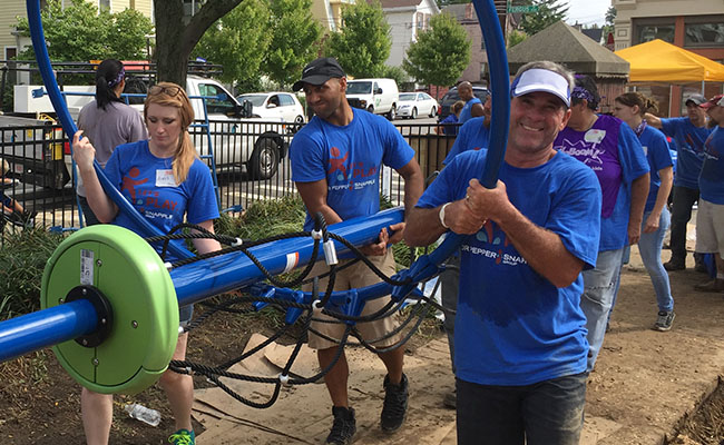 Employees of Dr Pepper Snapple, the 2016 Civic 50 sector leader for consumer staples, volunteer at a playground build. The company built or renovated more than 2,500 playgrounds and provided new sports equipment to hundreds of organizations in 2016. DPS employees also contributed more than 35,000 volunteer hours.