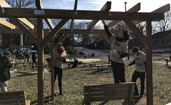 MLK Day 2018 volunteers stain a structure at a public space in Atlanta's English Avenue neighborhood, where several community revitalization projects are underway.