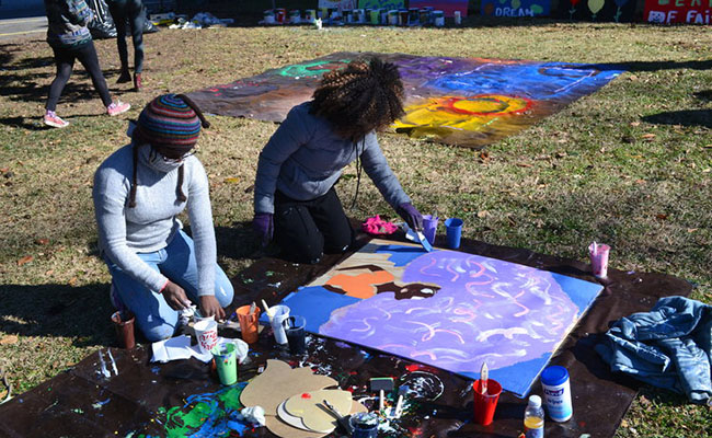 MLK Day 2018 volunteers painted boards with colorful pictures and inspiring messages, which would be hung on vacant buildings and homes in the English Avenue neighborhood. (Photo courtesy of Hands On Atlanta)