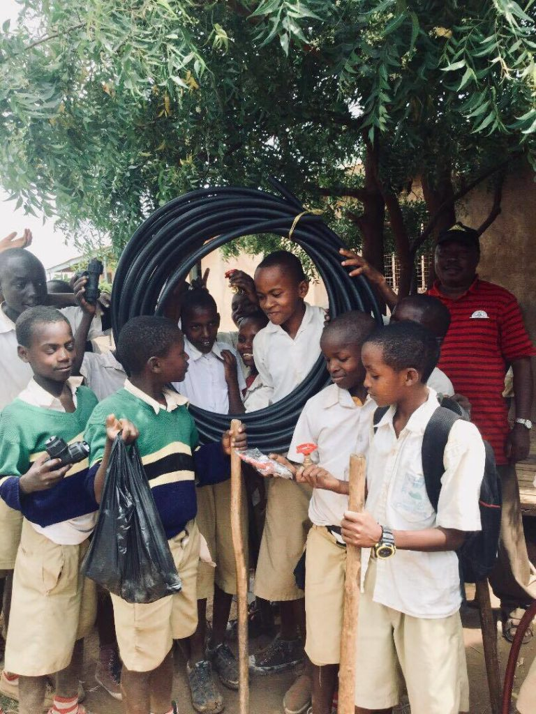 Students at Majengo School in Tanzania holding the supplies needed to make a proper handwashing station at their school. The project, started by a participant in Mahika's program, helped increase school attendance because fewer students were getting sick from not washing their hands./Courtesy Mahika Halepete