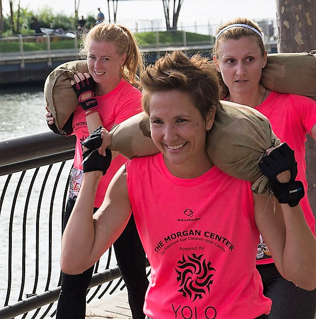 Danielle Taylor (center) carries a heavy sandbag while participating in a YOLO Strong obstacle course run./ Courtesy Danielle Taylor
