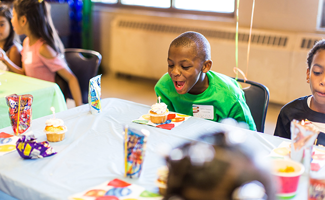 A celebrate! RVA child blows out his birthday candle and makes a wish.