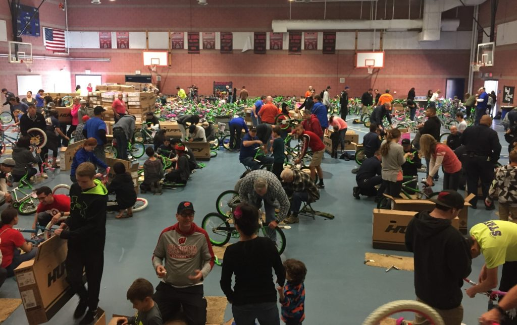 Hundreds of volunteers help to assemble bikes to donate to students for Bicycles for Children in the days leading up to delivery, before Christmas Day./Courtesy John White