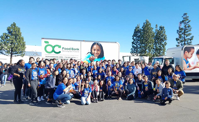 OneOC volunteers gather to pack thousands of boxes of food to be distributed.