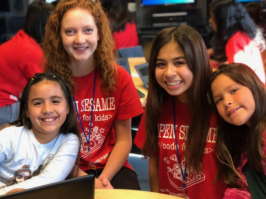 Katherine, left, and Milan pose with some of the over 300 children they have helped to teach coding to through Open Sesame./Courtesy Open Sesame