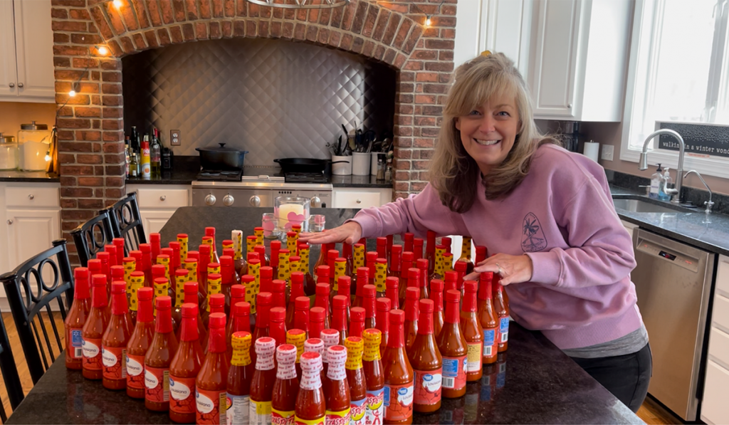 Daily Point of Light Award Honoree Kristen Weinberg shows off 50 bottles of hot sauce she collected to donate to a local soup kitchen through her What's Your 50? movement