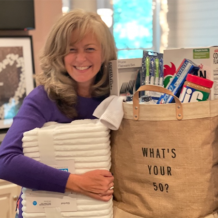 Daily Point of Light Award Honoree Kristen Weinberg poses with examples of items that can be donated as part of the What's Your 50? movement she started.